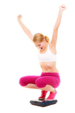 weight loss success: Slimming diet weight loss success. Happy joyful young woman girl on weighing scale raising her arms hands. Healthy lifestyle concept. Isolated on white background. Stock Photo