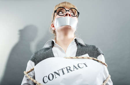 Afraid businesswoman bound by contract terms and conditions with mouth taped shut. Scared woman tied to chair become slave. Business and law concept. Reklamní fotografie