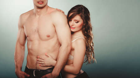 half naked: Sexy passionate couple in studio. Handsome half naked semi nude man and pretty woman in lingerie. Love and passion. Stock Photo