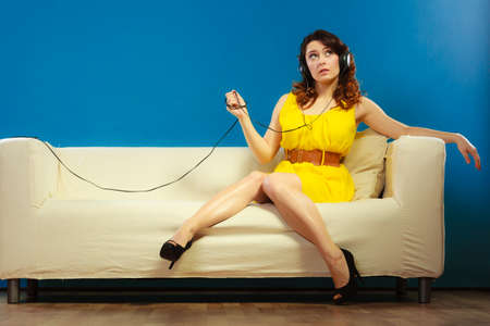happy teenagers: Young people leisure relax concept. Teen cute girl yellow dress in big headphones listening music mp3, sitting on couch relaxing on blue