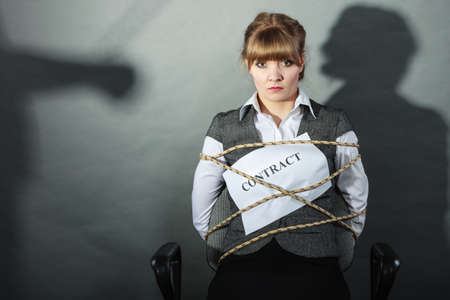 reluctance: Upset businesswoman bound by contract terms and conditions.  Helpless woman tied to chair become slave. Human shadow in background. Business and law concept.