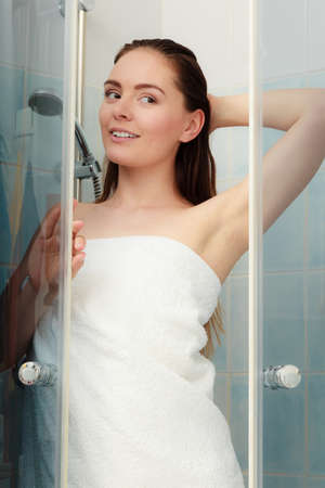 cubicle: Girl showering in shower cabin cubicle enclosure. Young woman with white towel taking care of hygiene in bathroom. Stock Photo
