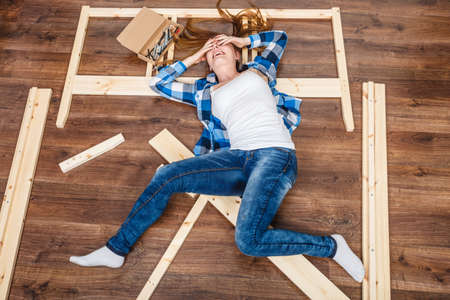 Happy woman having fun assembling furniture at home. Young girl laying on floor arranging apartment house interior. DIY. High angle view. Stock Photo