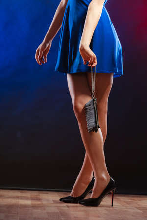 club dress: Celebration disco and evening fashion concept - woman in blue dress holding handbag bag, dancing in the club, part of body female legs in high heels on party floor