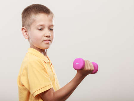 care about the health: Sports boy making exercise with dumbbell. Care about health and body Stock Photo