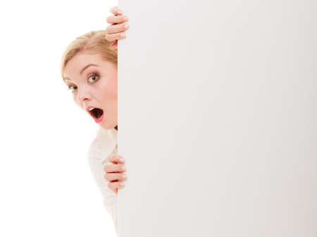 recommending: Advertisement. Surprised woman hiding behind blank copy space banner isolated on white. Businesswoman recommending your product