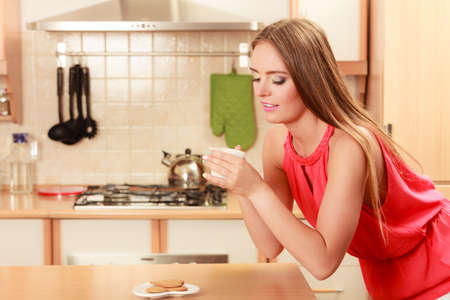stimulate: Pretty woman with heart shape gingerbread cookies drinking tea or coffee at home. Gorgeous young girl with hot beverage relaxing in kitchen. Stock Photo