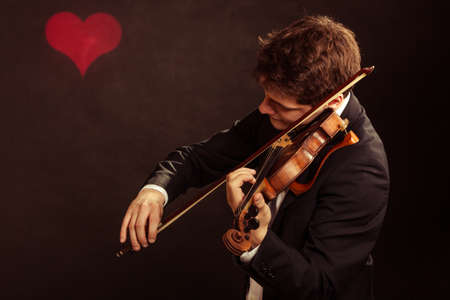 fiddler: Art and artist. Young elegant in love man violinist fiddler playing violin on black background with valentine heart love symbol. Classical music. Studio shot. Stock Photo