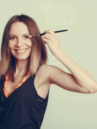 and eyelid: Woman stylist applying eyeshadow professional makeup brush. Girl beautifying eye eyelid. Make up makeover concept.