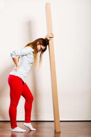 moving box: Unhappy tired woman moving into new apartment house carrying heavy carton box with furniture. Young girl arranging interior and unpacking. Female having backache pain. Stock Photo