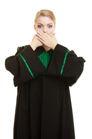 judicature: Confidential information. Law court or justice concept. Woman lawyer barrister wearing classic polish black green gown covering mouth with hands. Stock Photo