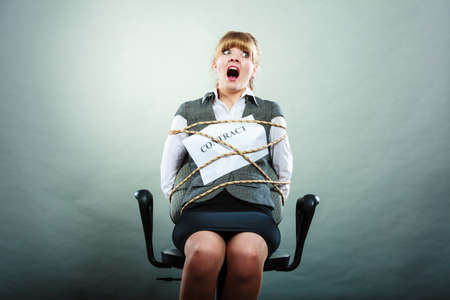 forced: Afraid businesswoman bound by contract terms and conditions. Screaming scared woman tied to chair become slave. Business and law concept.