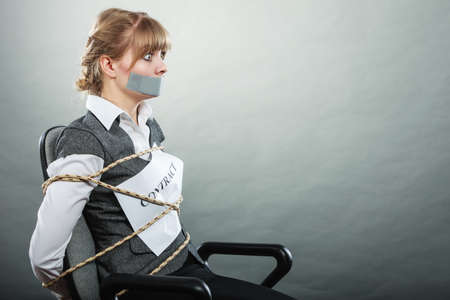 forced: Afraid businesswoman bound by contract terms and conditions with mouth taped shut. Scared woman tied to chair become slave. Business and law concept. Stock Photo