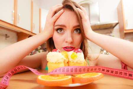 undecided: Undecided woman looking at delicious cake with sweet cream and fruits on top. Girl with tape measure trying to resist temptation. Slimming diet dilemma. Stock Photo