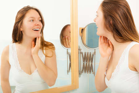 Happy young girl woman without makeup in bathroom standing in front of mirror smiling. Natural beauty. Purity. Stock Photo