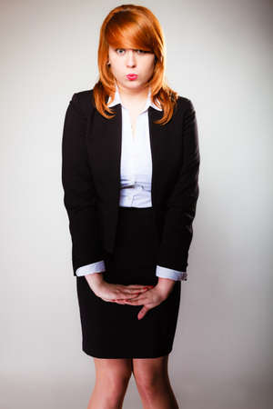 silly face: Portrait of funny redhair business woman or student girl making silly face. Studio shot on gray background Stock Photo