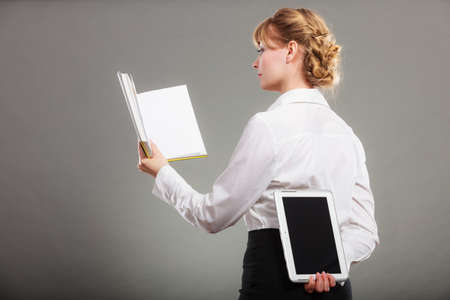 elearning: Woman learning with book holding ebook reader behind back. Choice between modern educational technology and traditional way method. Girl hold digital tablet pc and textbook. Contemporary education.