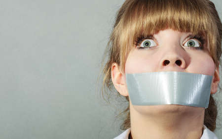 taped: Scared woman with mouth taped shut. Afraid young girl with duct tape on lips. Censorship and freedom of speech concept.