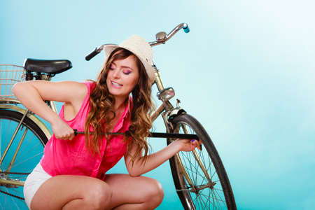 summer tire: Young woman pumping up tire tyre with bike bicycle pump. Summer recreation activity.