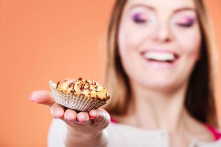 gula: Mujer feliz celebraci�n de la torta deliciosa de la magdalena. El apetito y el concepto de la gula.
