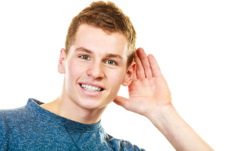 listening ear: Gossip. Young man holding hand to ear listening isolated on white background