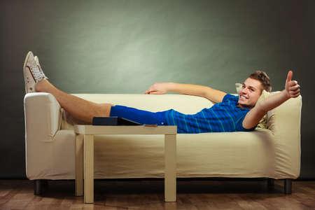 relajado: Hombre feliz joven se relaja en la toma de sofá pulgar hacia arriba la mano signo gesto, la tableta y el teléfono móvil poniendo sobre la mesa Foto de archivo