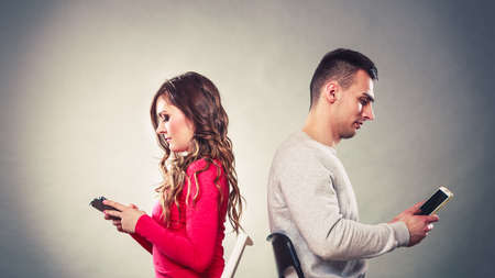 apart: Couple using mobile phones not talking to each other. Unhappy frustrated man and woman use new technology and grow apart.