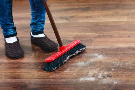cleanup: Cleanup housework concept. Closeup broom and female foots. Cleaning woman sweeping wooden floor. Stock Photo