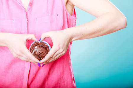 making love: Hands making heart shape holding delicious tasty sweet chocolate muffin. Confectionery food love.