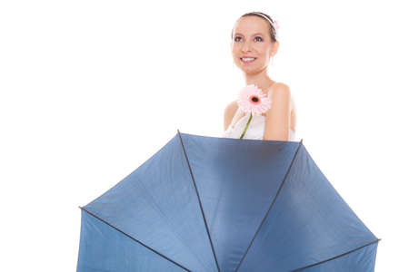ttractive: Happy ttractive pretty bride woman in white dress holding blue umbrella and gerbera flower. Happy smiling young girl during raining wedding day isolated on white background.