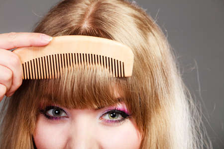 fringe: Fashion beauty and haircare concept. Closeup young woman refreshing her hairstyle girl combing her hair fringe with wooden comb Stock Photo