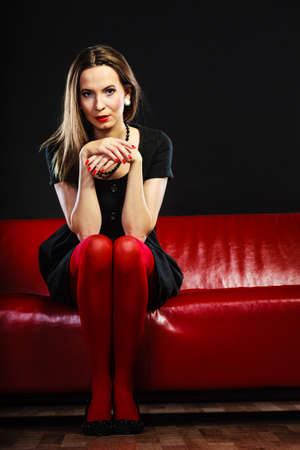 red couch: Elegant fashion outfit. Fashionable woman in vivid color pantyhose sitting on red couch indoor on black Stock Photo