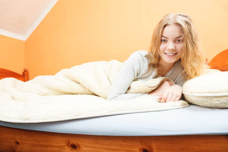 Woman waking up in bed in the morning after sleeping. Young girl laying under wool blanket. Reklamní fotografie