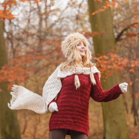 Fashion woman with flying scarf running in fall autumn park forest against blowing wind. Young girl in fur cap and sweater having fun outdoor.