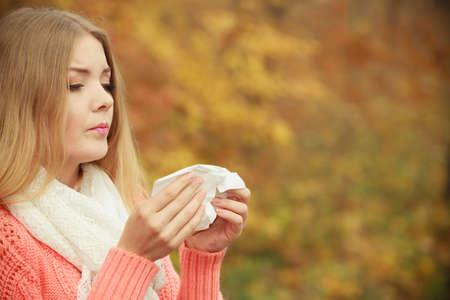 gripe: Mujer enferma en el otoño de parque del otoño estornudos en el tejido. Muchacha enferma atrapó al aire libre de la gripe frío. Rinitis o alergia. Cuidado de la salud. Foto de archivo