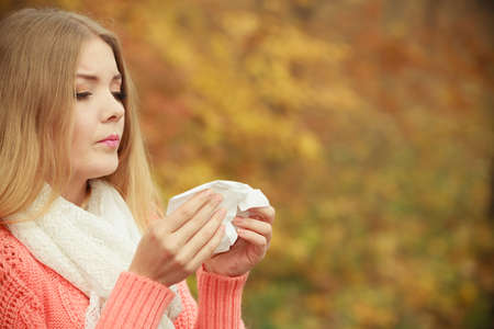 flu: Sick woman in fall autumn park sneezing in tissue. Ill girl caught cold flu outdoor. Rhinitis or allergy. Health care. Stock Photo