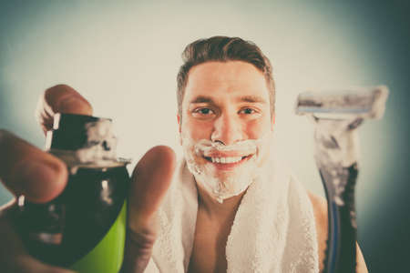 shaving cream: Handsome bearded young man with shaving cream foam can and razor preparing to shave. Skin care and hygiene.