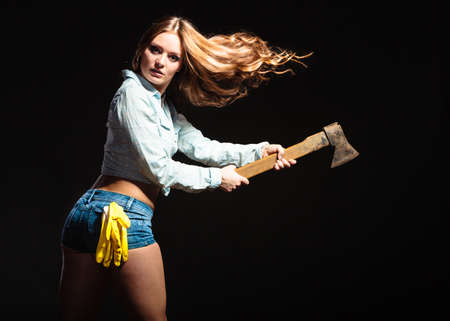 feministische: Sexy seductive woman holding axe chopper. Strong girl feminist working in man profession. Independent female.