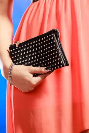 clutch bag: Fashion elegant evening outfit. Close up female hand holding black rivet leather handbag clutch bag