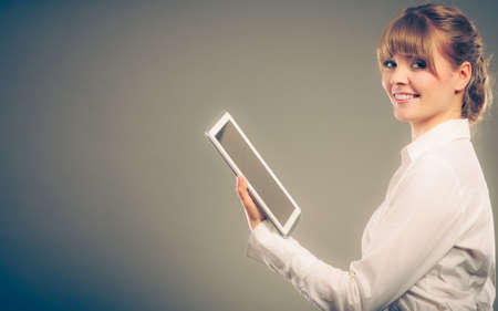 well read: Woman reading and learning with ebook digital tablet. Education leisure. Young girl in white shirt studying for exam.