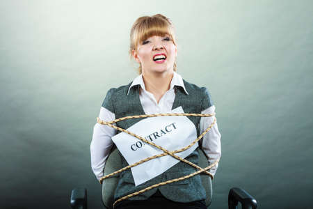 scared woman: Afraid businesswoman bound by contract terms and conditions. Screaming scared woman tied to chair becoming slave. Business and law concept. Stock Photo