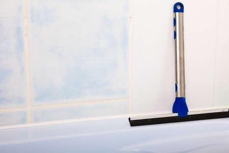 Squeegee. Window cleaning tool in bathroom.