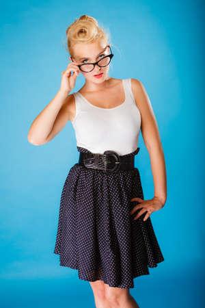 oculist: Optometrista, oculista y el concepto oftalmólogo. Joven rubia retro pin up sexy mujer con gafas en el fondo azul en el estudio.