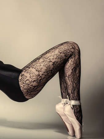 suppleness: beautiful woman ballet dancer, part of body legs in shoes and black lace tights studio shot on gray background