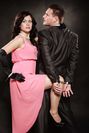 Detective theme. Retro style attractive couple, rich gangster in handcuffs and charming woman sexy detective spy on black background.