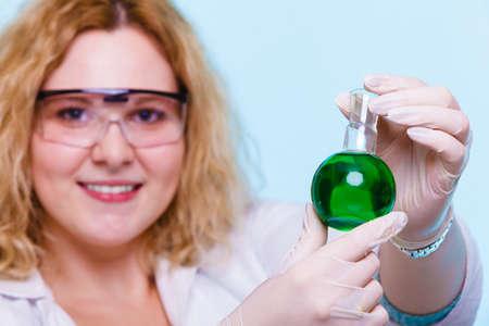 investigador cientifico: Experimento, la investigación en curso. Mujer del químico o niña estudiante, auxiliar de laboratorio o investigador científico con química matraz de ensayo de vidrio en azul