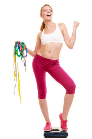 measures: Slimming and weight loss success. Happy young woman girl measuring with tape measures on weighing scale clenching fists. Healthy lifestyle concept. Isolated on white. Stock Photo