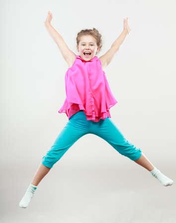 Emocionado niña feliz saltando de alegría en el aire. Cabrito alegre alegre en estudio con los brazos levantados hacia arriba. Foto de archivo - 46633102