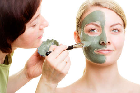 cosmetician: Beauty treatment concept. Cosmetician applying clay facial mask at woman face. Body care healthy lifestyle. Stock Photo