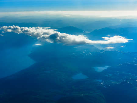 Birds eye. View from window of plane airplane flying over fjords Norway Scandinavia.